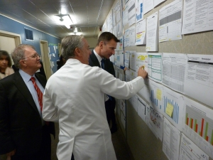 Virginia Mason Chairman and CEO Gary S. Kaplan, MD, shares information on the organization's Accountability Wall with British Secretary of State for Health Jeremy Hunt. (Photo courtesy of Robin Twyman.)